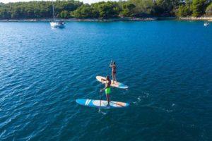 deux individus sur stand up paddle nahskwell skool avec eau calme